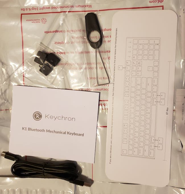 Contents of the box.  Key puller, manual, USB-A to C cable, key caps and a keyboard layout diagram.